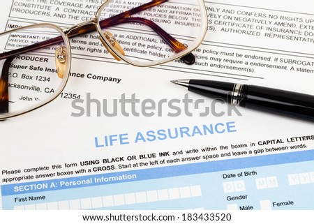 Life assurance application form with pen and glasses concept for life planning