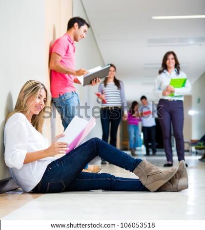 Life at university with students walking the corridors - stock photo