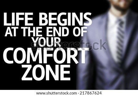 Life Begins at the end of Your Comfort Zone written on a board with a business man on background - stock photo