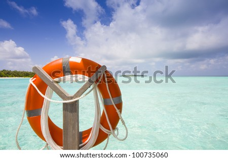 life belt at the sea with island blue sky and clouds - stock photo