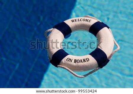 Life buoy floating in the two colored swimming pool in dark and light blue - stock photo