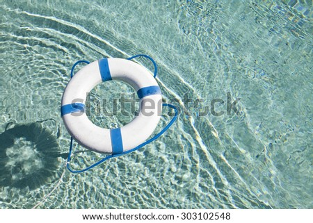 Life buoy  in a  clear blue swimming pool water - stock photo