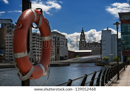 Life buoy in the foreground and buildings at liverpool dock in the background. Image no 144. - stock photo