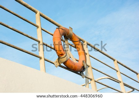 LIFE-BUOY ON HANDRAIL OF FERRY BOAT, CLEAR BLUE SKY BACKGROUND - stock photo
