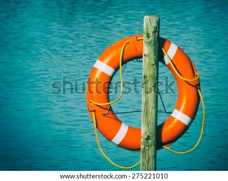 Life buoy on wooden pole against lake, retro toned with dark vignette - stock photo