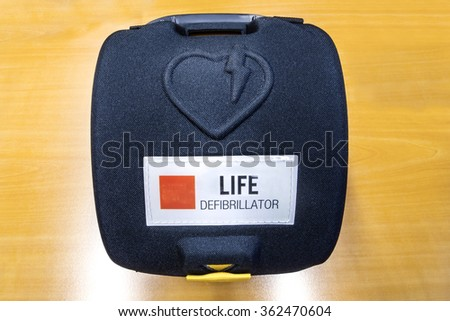 Life defibrillator, Automatic External hart defibrillator pack on the wooden color office desk - stock photo