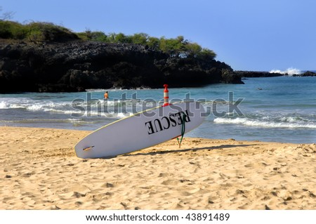 Life guard surf board sits ready for action.  The word Rescue is painted in black on the board. - stock photo