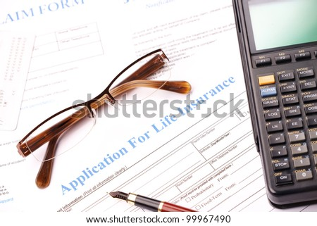 Life insurance application form with fountain pen, glasses and calculator - stock photo