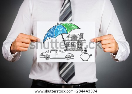 Life insurance concept. Businessman holding paper with drawing of a house, car and money symbols under the umbrella. - stock photo