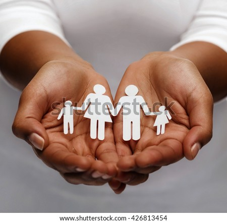 life insurance, love and charity concept - closeup of womans cupped hands showing paper man family - stock photo
