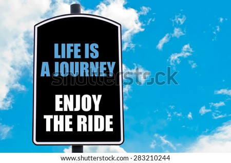 LIFE IS A JOURNEY ENJOY THE RIDE  motivational quote written on road sign isolated over clear blue sky background with available copy space. Concept  image