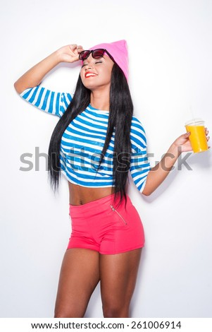 Life is beautiful and colorful! Cheerful young African woman in funky clothes carrying glass with orange juice and keeping eyes closed while standing against white background - stock photo