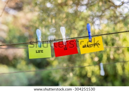 Life Is Beautiful concept with the words hanging on three green, red and yellow cards from a clothes line by plastic pegs over a leafy green nature background. - stock photo