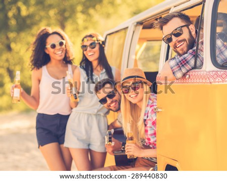 Life is brighter when friends are near. Group of cheerful young people enjoying time together while sitting and standing near their retro minivan  - stock photo