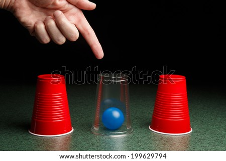 Life is easy when you know the answers.  Location of blue ball is revealed by clear cup and pointing hand.  Copy space. - stock photo