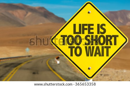 Life Is Too Short To Wait sign on desert road - stock photo