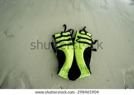 Life jacket on sand,life jacket save your life,Beach umbrellas, chairs, and life jackets on deserted beach. - stock photo