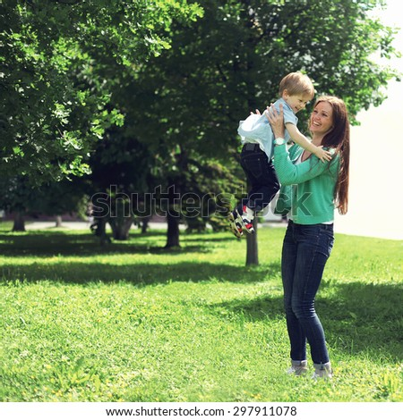 Life moment of happy family! Mother and son child playing having fun together outdoors at the weekend on the grass in sunny summer day - stock photo