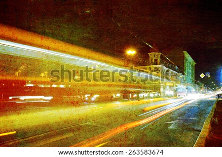 life of the old city at night with lights and a passing public transport - stock photo