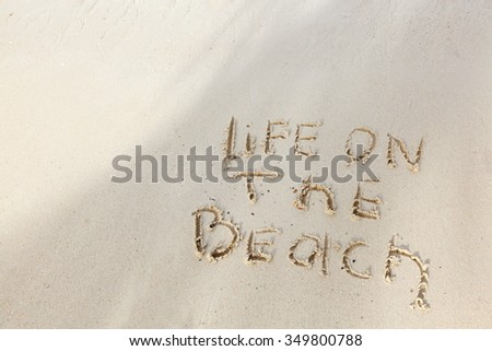 Life on the beach concept - inscription on a beach sand with coming wave - stock photo
