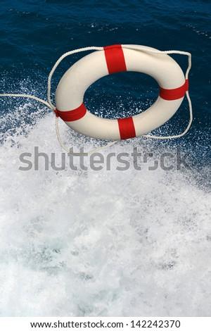Life preserver thrown into splashing water - stock photo