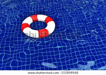 Life ring floating on top of sunny blue water in pool - stock photo