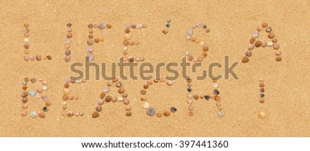 life´s a beach - written on the beach using individual seashells in the brown sand