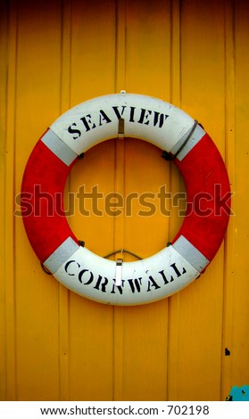 Life Saver on a boat's yellow wall. - stock photo