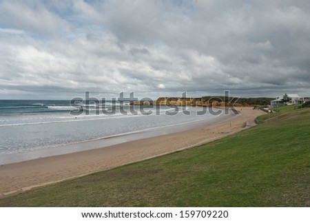 Life savers club building and Torquay beach with green grass, sandy beach, surfers in water and cloudy sky in background in Victoria, Australia - stock photo