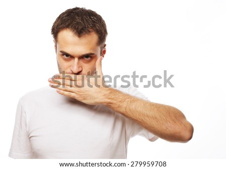 life style  and people concept: Shocked young man  covering mouth with hands and looking at camera while standing against white background - stock photo