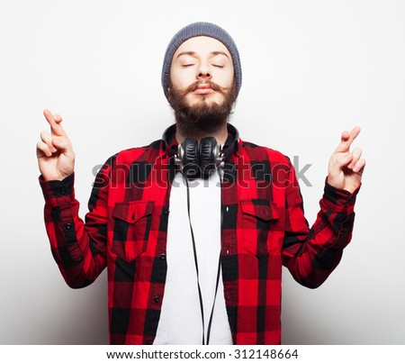 life style and people concept:Waiting for special moment. Portrait of young bearded man in shirt keeping fingers while standing against white background. Hipster style and positive emotions. - stock photo