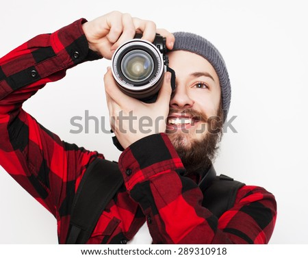 life style, tehnology and people concept: professional photographer. Portrait of confident young man in shirt  holding  camera over white background - stock photo