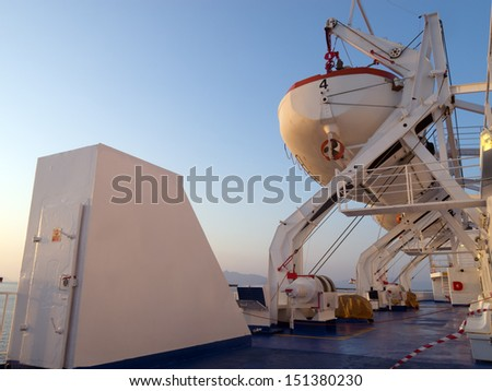 Lifeboat attached to big cruise ship for emergency cases - stock photo