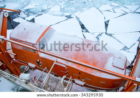 Lifeboat on board of the ship going through the ice in Arctic ocean  - stock photo