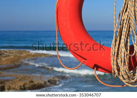 Lifebuoy and rope close-up on a background of the rocky coast. horizontal