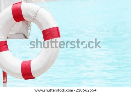 Lifebuoy hanging on a pole in swimming pool - stock photo
