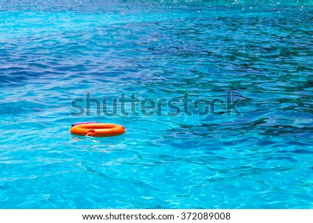 Lifebuoy in a stormy blue sea - stock photo