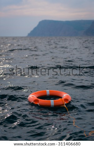 Lifebuoy in ocean near mysterious blurred continent in the evening