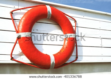 Lifebuoy on a wooden wall - stock photo