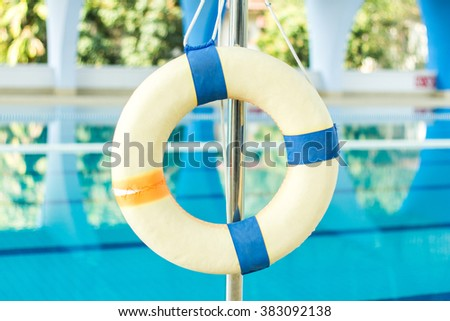 Lifebuoy on soft swimming pool background - stock photo