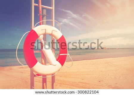 Lifebuoy, Red and White Life Preserver on Sandy Beach of Coastal Summer Vacation Resort, Vintage Retro Toned Image - stock photo