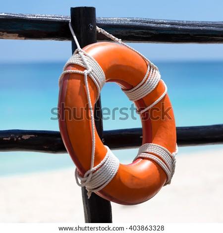 Lifebuoy ring on wooden railing near tropical beach - stock photo