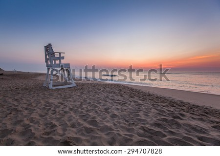 Lifeguard Chair at Coast Guard Beach just before sunrise.  Ocean waves forming near shore.  Eastham MA, Cape Cod - stock photo