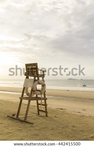 Lifeguard chair on the beach with cloudy sky in the warm morning light
