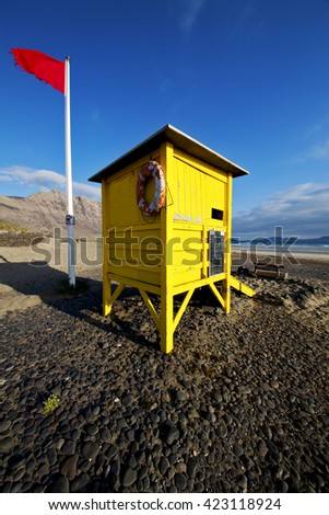 lifeguard chair red flag in spain  lanzarote  rock stone sky cloud beach  water  musk pond  coastline and summer  - stock photo