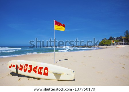 Lifeguard flag and board against blue sky - stock photo