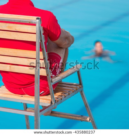 Lifeguard on duty, sitting in chair above swimming pool