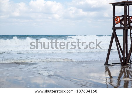 Lifeguard platform and lookout with an attached life buoy or ring on a tidal beach overlooking breaking ocean waves - stock photo