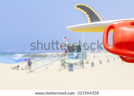 Lifeguard red buoy on a beach with lifeguard tower in distance, shallow depth of field, space for text, California, USA. - stock photo