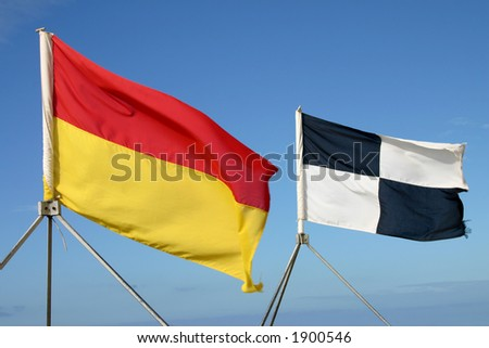 Lifeguard's safety yellow and red swimming flag, black and white surfing flag, Cornwall, UK - stock photo
